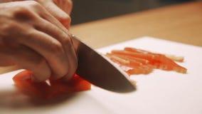 Kokhanden die in Spaanse pepers op een scherpe raad worden gesneden Het concept gezond stock videobeelden
