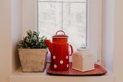 Kokkärl med sockerbunken på fönstret på köket arkivfoto