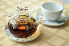 Kokkärl med svart te på tabellen Fotografering för Bildbyråer