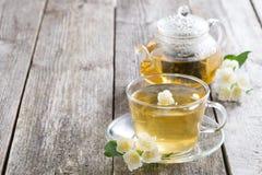 Kokkärl och en kopp av grönt te med jasmin på träbakgrund Royaltyfria Bilder