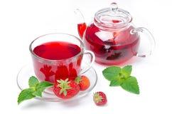 Kokkärl och en kopp av rött te med den isolerade jordgubbar och mintkaramellen Royaltyfri Bild