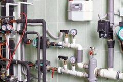 Kokkärl och rör av uppvärmningsystemet av ett hus arkivfoto