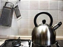 Kokkärl på en gasugn och rivjärn på väggen royaltyfria bilder