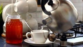 Kokkärlet är kokande, och flickan gör te arkivfilmer