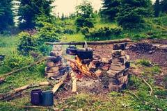 Kokkärlet och den lilla kokkärlet värmas på en brasa arkivbilder