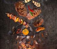 Kokkärlgaller med varma briketter, gjutjärnspisgallret och smakliga kött som flyger i luften Royaltyfri Foto