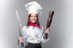 Kokmeisje die een reusachtige mes en een peper houden royalty-vrije stock afbeeldingen