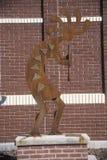 Kokopelli雕象,有砖墙的格查尔上帝在背景中 库存图片