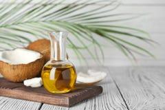 Kokosnöt och olja i flaska på trätabellen laga mat som är sunt arkivbild