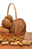 Kokosnöten kiwien, jordnöt i korgen på det trä stiger ombord Royaltyfria Bilder
