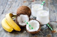 Kokosnöten mjölkar smoothiedrinken med bananer på träbakgrund Arkivbild