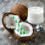 Kokosnöten mjölkar smoothiedrinken på träbakgrund royaltyfria bilder