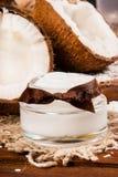 Kokosnöten och den hemlagade kokosnöten lagar mat med grädde på en träbakgrund Arkivbild