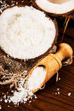 Kokosnöten och kokosnöten gå i flisor på en träbakgrund Arkivfoton