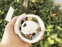 Kokosnötglass med blandningmuttrar i handhåll Arkivfoto