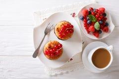Kokosnötmuffin med bär och kaffe med mjölkar närbild på th Royaltyfri Fotografi