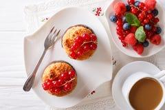 Kokosnötmuffin med vinbär och kaffe med mjölkar närbild på t Royaltyfri Fotografi