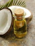 Kokosnötolja i en glasflaska och muttrar Royaltyfri Bild