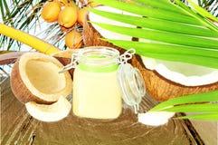 Kokosnötolja med den klippta kokosnöten och sidor Arkivbilder