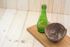 Kokosnötskal med gröna glasflaskor på splat Arkivbild