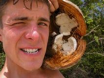 Kokosnötskalet att få river av av En man rev sönder en kokosnöt som lider hunger Extraktion av mat på enbebodd ö arkivbilder