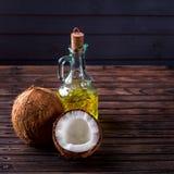 Kokosnötter en flaska av olja på en mörk träbakgrund Royaltyfri Fotografi