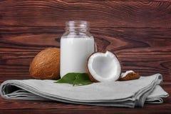 Kokosnötter och mjölkar på ett grått stycke av torkduken på en träbakgrund Nya snittkokosnötter och en glasflaska av läckert mjöl Royaltyfri Foto