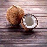 Kokosnötter på en mörk träbakgrund Arkivfoto
