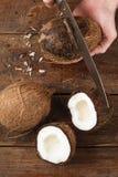 Kokosnüsse geschnitten auf braunen hölzernen Hintergrund Lizenzfreie Stockfotos