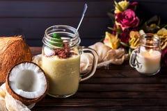 Kokosnüsse und Püreee von den tropischen Früchten mit Schokolade auf woode Stockbild