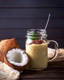 Kokosnüsse und Püreee von den tropischen Früchten mit Schokolade auf woode Stockbilder