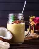 Kokosnüsse und Püreee von den tropischen Früchten mit Schokolade auf woode Stockfotografie