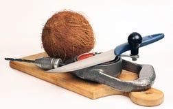 Kokosnoot op een scherpe raad. Een mes en een boor Stock Foto's