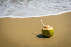 Kokosnoten met het drinken stro op het zand Stock Foto's