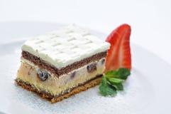 Kokosnotencake met marsepein en aardbei op witte plaat, fotografie voor winkel, patisserie stock afbeelding