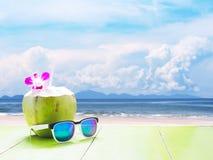 Kokosnotendrank en zonnebril op de achtergrond van het de zomerstrand Stock Fotografie