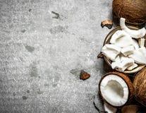 Kokosnötträmassa i en bunke och hela kokosnötter Royaltyfri Bild