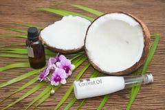 Kokosnussöl in den Flaschen mit frischen Kokosnüssen Stockbild