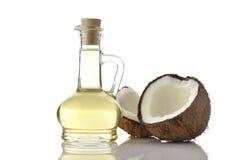 Kokosnussöl mit Kokosnüssen auf weißem Hintergrund Lizenzfreies Stockbild