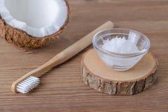 Kokosnussölzahnpasta, natürliche Alternative für gesunde Zähne, hölzerne Zahnbürste stockfoto