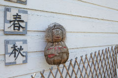 Kokosnuss-Affe auf Gitter-Zaun mit japanischen Symbol-Fliesen Lizenzfreies Stockbild