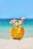 Kokosnuss mit Strohen und bunten Cocktailregenschirmen auf einem tropica Lizenzfreies Stockfoto