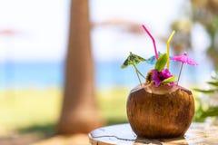 Kokosnuss mit Trinkhalm, Regenschirmen und Blumen Stockfoto