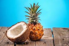 Kokosnuss und Ananas auf dem Holztisch lokalisiert auf blauem Hintergrund Stockfotos