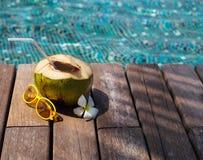Kokosnusscocktail mit Trinkhalm durch den Swimmingpool Stockfoto