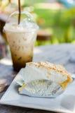 Kokosnusskuchen auf Tabelle mit Eiskaffee Stockfotografie