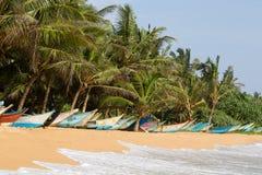 KokosnussPalmen und hölzerne Boote auf dem Sand setzen auf den Strand Lizenzfreie Stockbilder