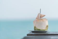Kokosnusssaft auf Tabelle in unscharfem Strandhintergrund Lizenzfreies Stockfoto