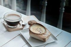 Kokosowy Creme Brulee jest cukierkowymi smakami i napojem z gorącego americano czarną kawą na białym drewnianym stołowym tle obrazy stock