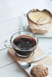 Kokosowy Creme Brulee jest cukierkowymi smakami i napojem z gorącego americano czarną kawą na białym drewnianym stołowym tle obraz stock